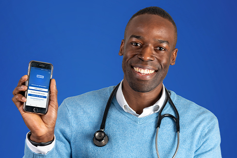 Abu holding a phone with the NHS App open