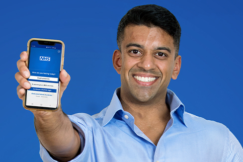 Arun holding a phone with the NHS App open