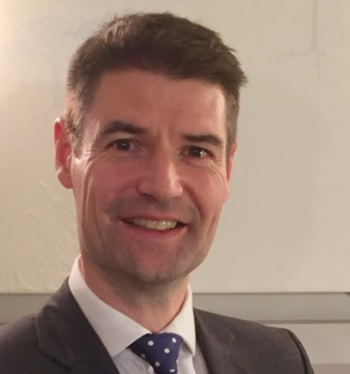 Head and shoulders of Dr Simon Eccles in a suit and tie