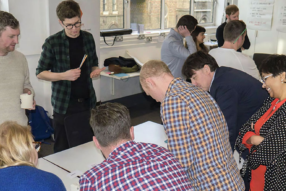 Designers workshop design principles sitting and standing around a table
