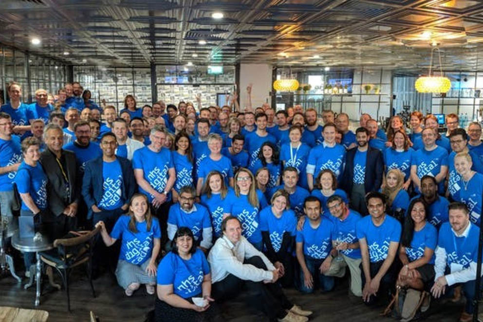 Members of the NHS Digital Academy cohort 1 take part in a group photograph wearing blue t-shirts