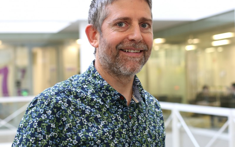 photo of Charles Creswell wearing flowery shirt with corporate atrium background