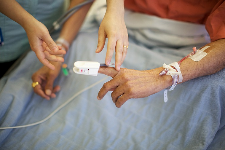 A patient's finger being hooked up to a monitor in a hospital bed