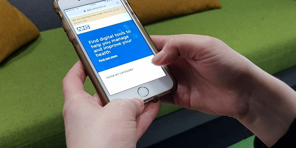 A person holding a smartphone accessing an NHS mental health app