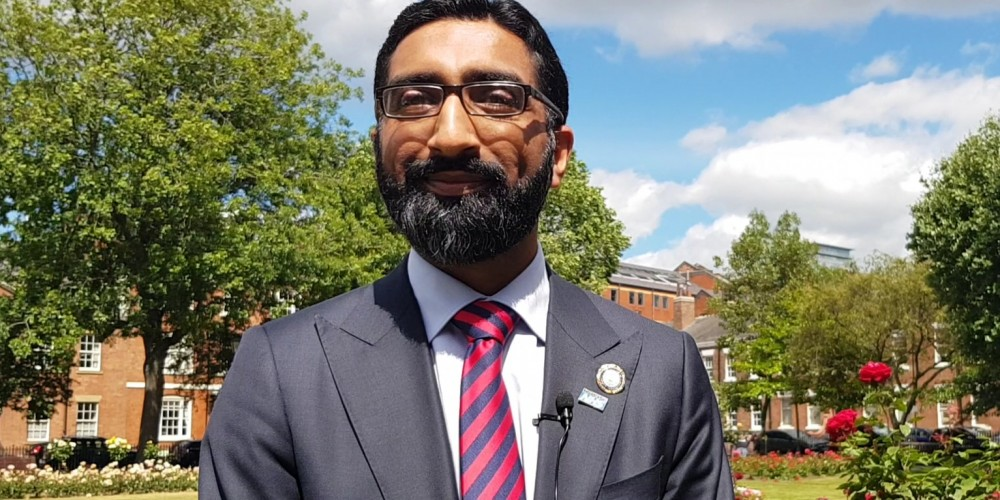 Mohammed Hussain outside dressed in suit and red tie
