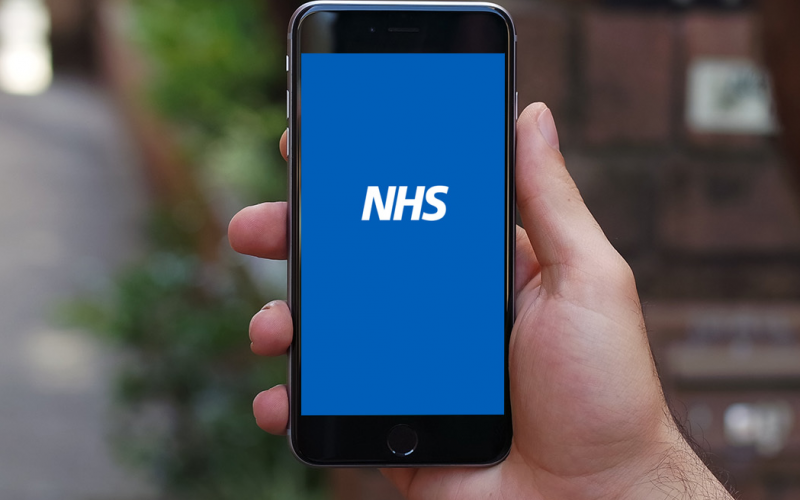 Smartphone with NHS logo in the centre of its screen on plain blue background