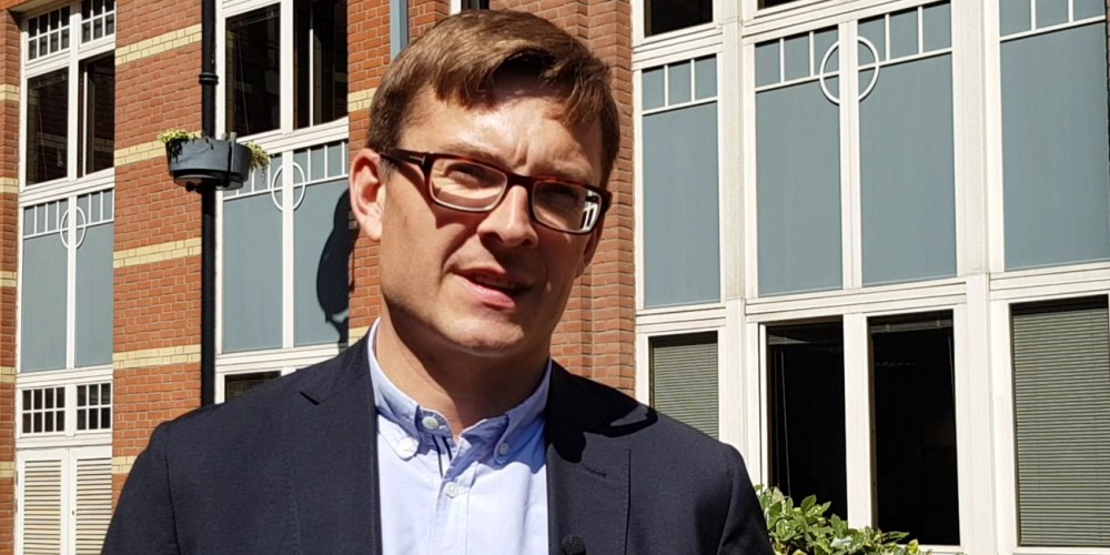 Head and shoulders photo of Nick Venters wearing glasses, suit and open neck shirt
