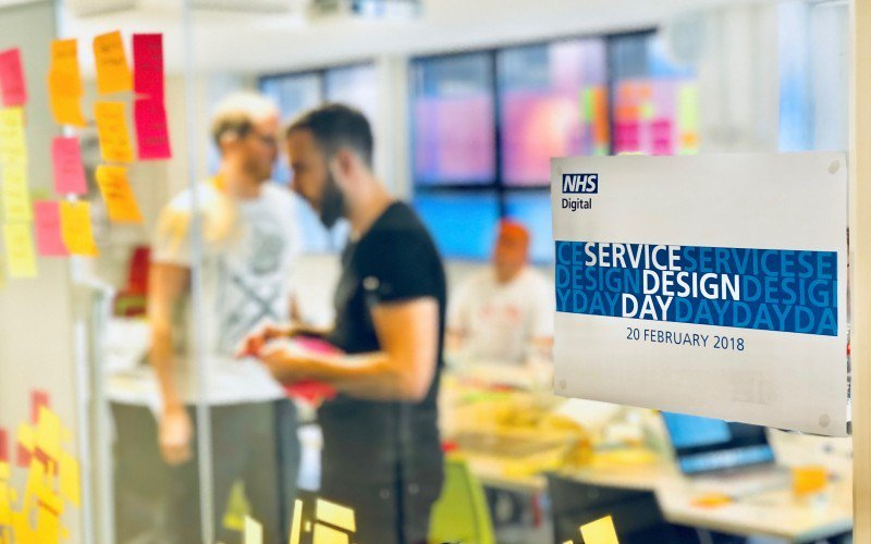 Service designers work behind a sign that reads NHS Digital Service Design Day