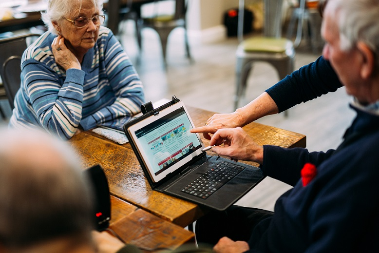 Elderly people being shown how to access healthcare info on a laptop