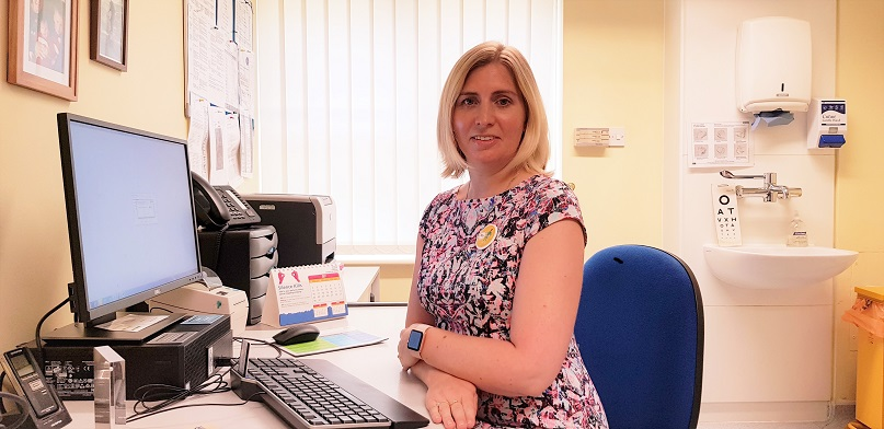GP Dr Kirsty Gillgrass sitting in her chair by her desk in her surgery room